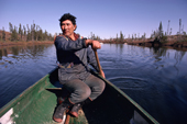 Cree Trapper, Abel Brien paddles his canoe while out hunting in the autumn. Quebec, Canada. 1988