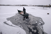 Abel Brien, a Cree hunter, breaks the ice on a frozen lake with his boat. Quebec. Canada. 1988