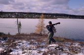 Cree hunter, Abel Brien, walking beside a frozen lake as he checks his traps out on the taiga. N.Quebec, Canada. 1988
