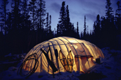 The light from a kerosene lamp illuminates a Cree winter tent in boreal forest. Quebec, Canada. 1988