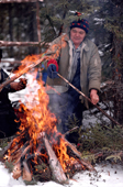 Cree woman, Elizabeth Brien, sets a pan of water to boil over a wood fire. Quebec, Canada. 1988