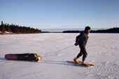 Billy Edwards, an elderly Cree in snowshoes, hauling a birchwood sled over lake ice. Quebec, Canada. 1988