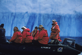 Red jacketed tourists in a zodiac cruise between vivid icebergs. Antarctica.