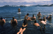 Tourists take a swim in the geothermal springs at Deception Island, Antarctic Peninsula.
