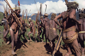 Yali warriors, wearing head- dresses and carrying bows & arrows, dance at a feast. Irian Jaya, Indonesia. 1990