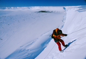 Cathy Moore abseiling down cliffs of Brunt Ice Shelf to Emperor Penguin colony at Windy Cove, Halley Research Station.  Antarctica.