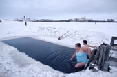 Bathers of the Walrus Club swimming during February in a hole in the ice covering Lake Semyonovskaya. Murmansk, NW Russia. 2005