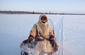 Olga Kirillova, a Sami woman from Lovozero, sits on her snowmobile during a break in a winter journey. Murmansk, NW Russia. 2005
