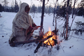 Olga Kirillova, a Sami woman from Lovozero, warms her hands by a fire during a break in a winter snowmobile journey. Murmansk, NW Russia. 2005