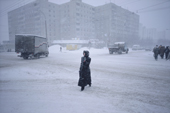 A woman walks in the centre of Murmansk during a winter snow storm. Kola Peninsula, NW Russia. 2005