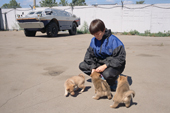 Dog handler, Eleana Batayeva, plays with puppies thart are part jackal and will later be trained to detect explosives at Sheremetyevo Airport, Moscow, Russia. 2005