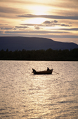 Two Sami men out checking their fishing nets in a wooden boat at sunset near Lovozero (Strong Lake). Kola Peninsula, NW Russia. 2005