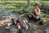 Valery Yuriev, a Sami man from Lovozero, sits by an open fire at a summer fishing camp. Kola Peninsula, NW Russia. 2005