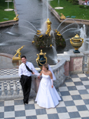 Wedding couple, with golden fountains and the Great Canal behind. Peterhof Palace. Near St. Petersburg, Russia. 2010