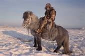 A Yakut horse herder riding in the winter time near Verkhoyansk. Yakutia, Siberia, Russia.