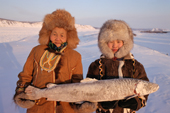 An elderly Evenk woman & a young Evenk girl holding a frozen fish. Northern Yakutia, Siberia, Russia. 2001