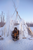 An Evenk woman leaving a traditional reindeer herders winter tent (Tordok). Kusur, N. Yakutia, Siberia, Russia. 2001